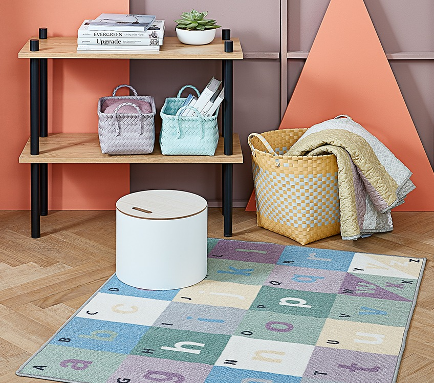 Room with kids rug on the floor, storage box and basket with throw