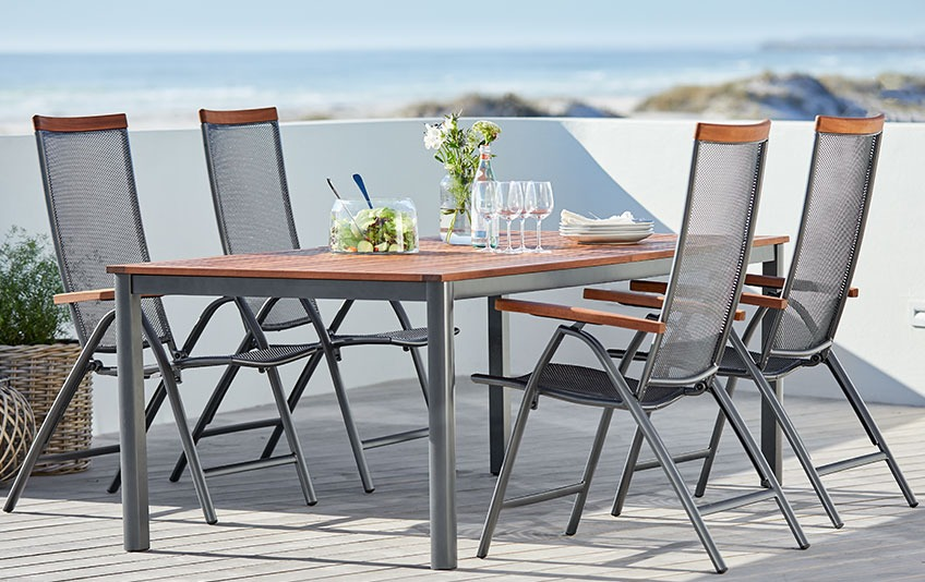 Garden furniture out of metal and hardwood on a patio