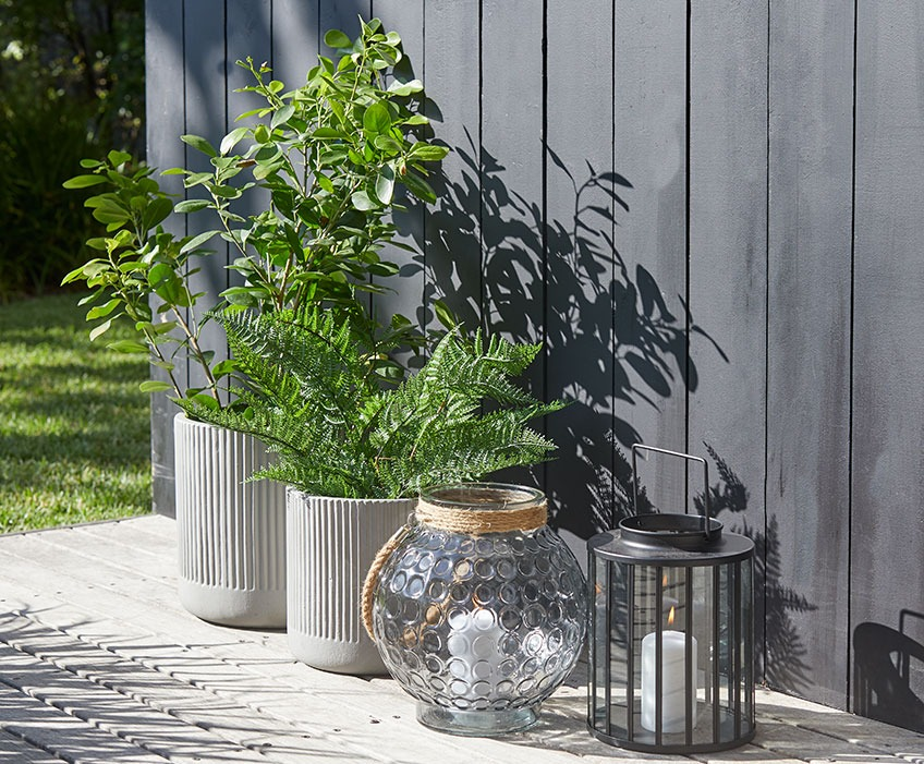 Small and large garden pots and two lanterns on a sunny patio