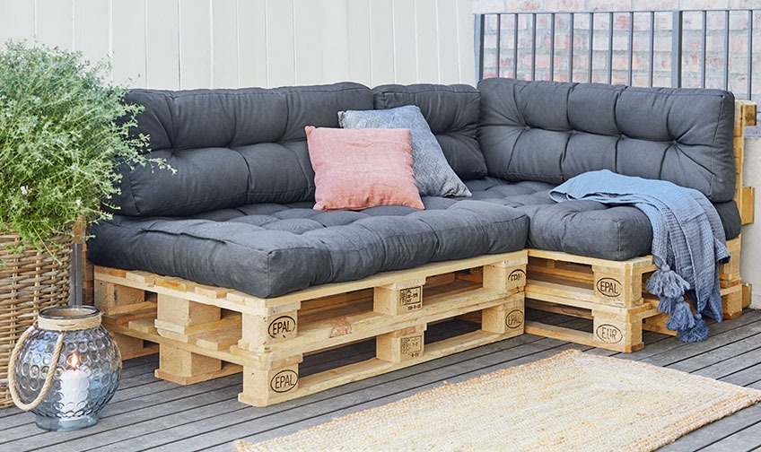 Pallet sofa with cushions and throw on a patio