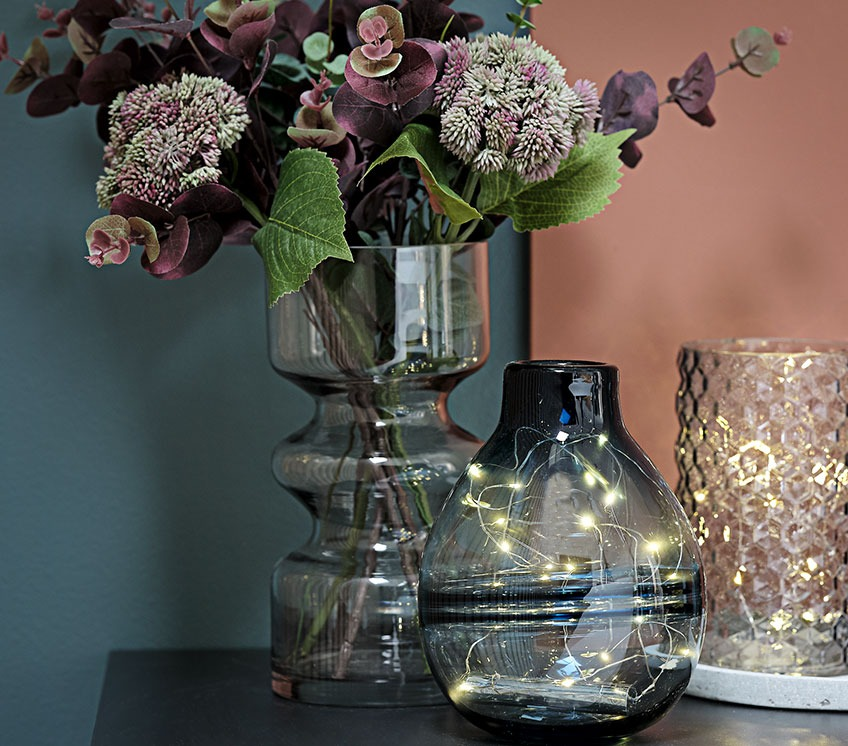 Collection of vases with light strings and artificial flowers