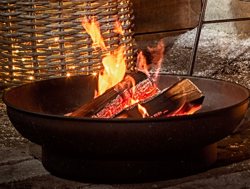Outdoor fire pit with burning logs on a patio