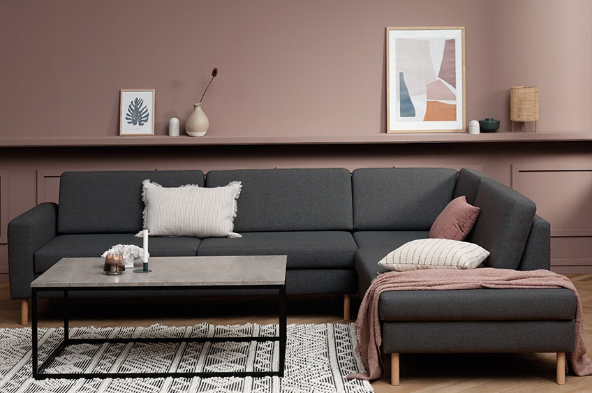Sofa with chaise end, cushions and throw in a living room