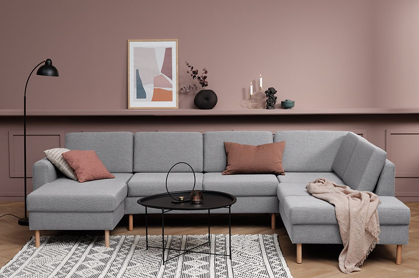 Large grey corner sofa with cushions and a throw in a modern living room